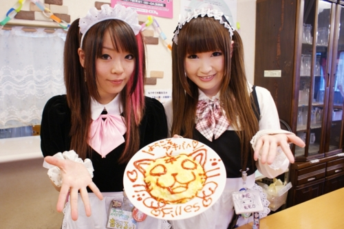 """Fig. 10. Two typical maid café waitresses donning their maid uniforms and displaying what appears to be a crêpe dish decorated with the image of a cat. Difficult to read, the decorative text appears to be giving a welcome message, followed by the image of a cat (neko), followed by the French word """"filles"""" (girls). Some maid uniforms might be accentuated with cat ears and tails (nekomimi). Japan Powered, accessed April 21, 2020. https://www.japanpowered.com/otaku-culture/what-are-maid-cafes."""